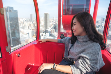 A beautiful asian woman riding a red ferris wheel in Japan
