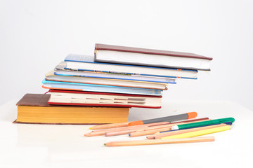educational books lie in a stack in the form of a ladder on the table, beside scattered multicolored pencils, pens and markers