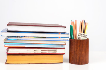 a neat stack of colorful Books with School supplies on table
