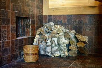 logs and a bucket of water stand by the fireplace in the bathhouse