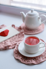 Cup of scented pink tea on crocheting napkin, teapot and envelope on windowsill. Valentines day. Romance Good morning
