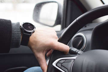 Man hand driving car holding steering wheel inside auto, modern black sport watch on wrist. Transportation and traveling concept.