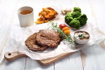 Mięso z grilla z pieczonymi ziemniakami i zielonymi warzywami.