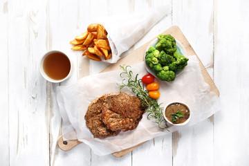 Smażony kotlet wieprzowy.  Kotlet z grilla z pieczonymi ziemniakami i zielonymi warzywami.