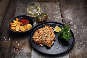 Ryba w migdałach. Smażony karp w panierce z płatków migdałowych, podany z brokułem, surówką z białej kapusty i kieliszkiem wina.