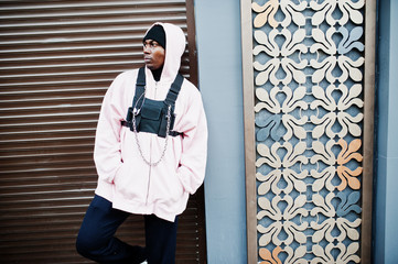 Stylish urban style african american man in pink hoodie posed. Afro rapper guy.