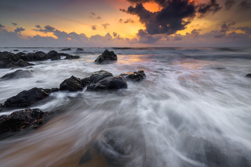 A scenery of sunrise with amazing unique rock formation and beautiful  flow of wave at Kemasik beach, Terangganu Malaysia. Soft focus during long exposure shot.