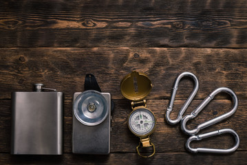 Compass, carabiner, flashlight and water flask on the brown wooden board background with copy space. Travel or adventure.