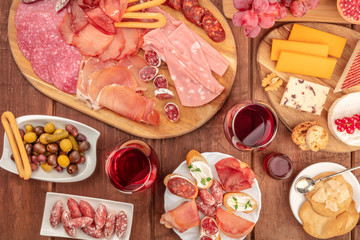 Gourmet Charcuterie. An assortment of sausages and hams, deli meats, and a cheese platter, shot from above on a rustic background with wine and olives