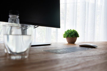 wood office table with single flower pot and mineral water in office room.