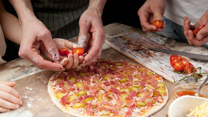 Horizontal Food Banner. Moms, daughters and son hands cook homemade pizza together. Close-up