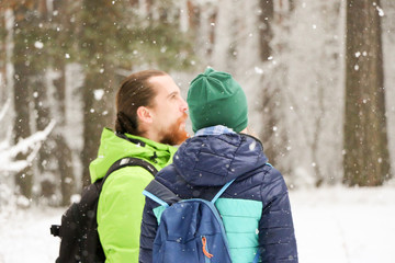 People walk in the woods in the winter. A lot of snow, fairytale nature. Boy and girl. A young couple.