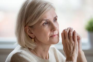 Portrait of sad woman cogitating sitting at home alone
