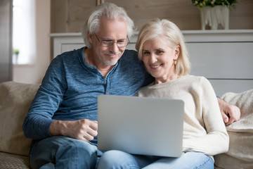 Aged couple sitting on couch watching movie on computer