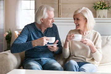 Smiling couple middle aged people sitting on couch drinking tea