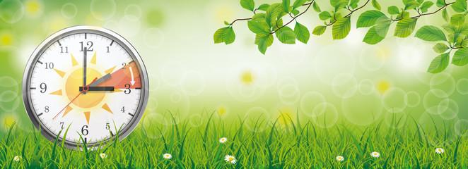 Zeitumstellung Sommerzeit Banner - Uhr auf einen Frühlingswiese