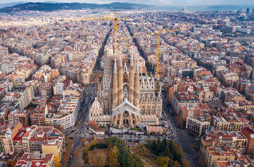 "Aerial; drone view of main Gaudi project Sagrada Familia Temple; majestic building towering over the rooftops of Eixample district; long construction of the temple ""business card"" of Barcelona, Spain"