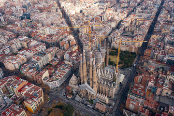 Aerial; drone view of main Gaudi project Sagrada Familia Temple; majestic building towering over the rooftops of Eixample; sharp domes and unusual forms of the great unfinished work of neo-gothic art