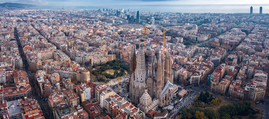 Aerial; drone view of main Gaudi project Sagrada Familia Temple; majestic building towering over the rooftops of Eixample district; one of the famous attraction for tourists and travelers in Barcelona