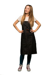 Full body Young woman with apron posing with arms at hip and laughing on isolated background - fototapety na wymiar