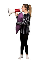 Full body Pretty woman in pajamas shouting through a megaphone to announce something in lateral position on isolated background