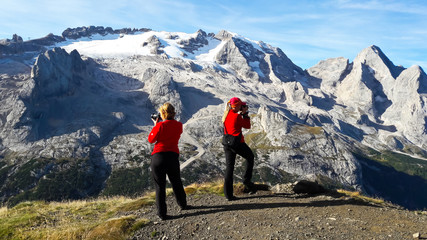 Two young women tourists taking picture of mountain landscape.  Marmolada Glacier. Dolomiti, Itay. Alps