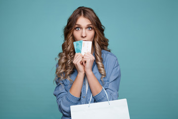 Nice picture of pretty model on blue backgrownd posing with credit cards and shopping bags