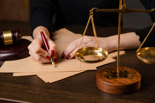 Young lawyer woman with bright red maniqure sitting at table and writing something by pen, lawyer woman with bright red nails working in office