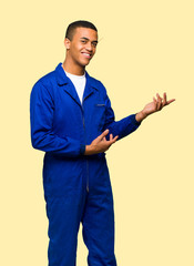 Young afro american worker man extending hands to the side for inviting to come on isolated background