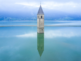 Aerial shot by drone of the Bell tower of Reschensee