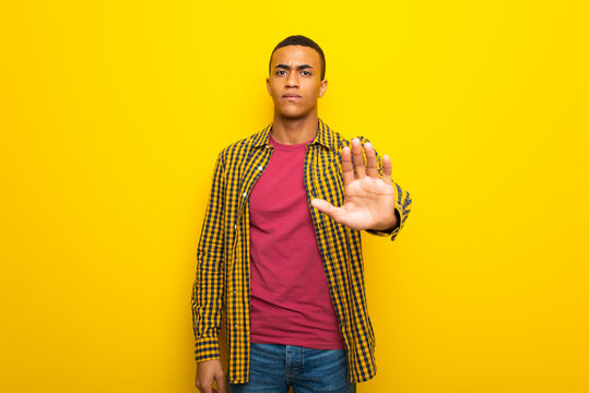 Young afro american man on yellow background making stop gesture denying a situation that thinks wrong