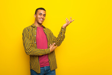 Young afro american man on yellow background extending hands to the side for inviting to come