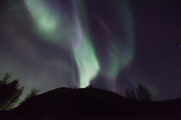 northern lights in Norway in green, blue and violet colours and a silhouette  of a mountains in front