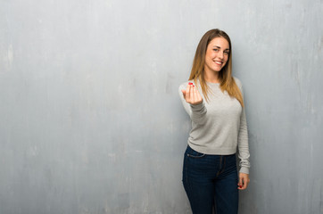 Young woman on textured wall inviting to come with hand. Happy that you came