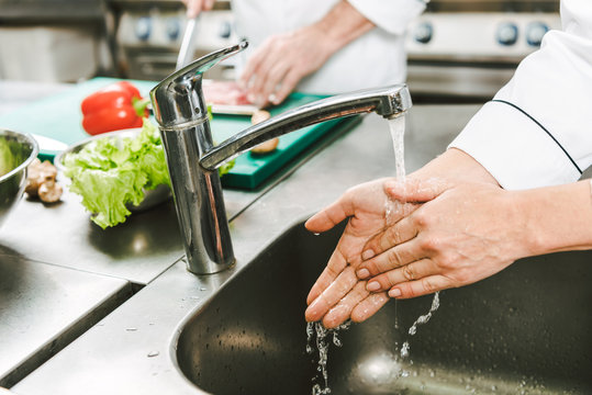 cropped view of female chef washing hands over sink in restaurant kitchen