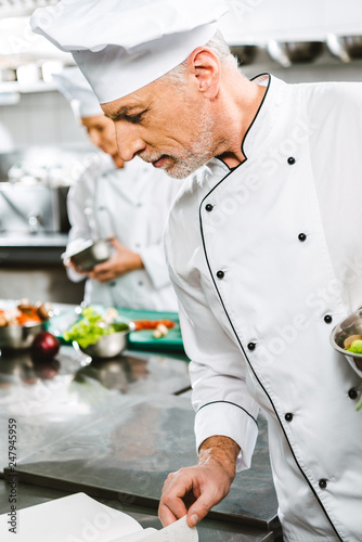 male chef in uniform and hat reading recipe book in restaurant