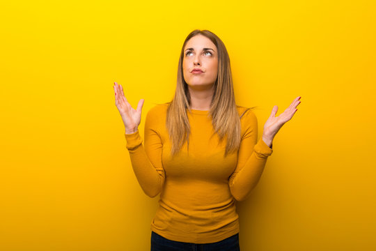Young woman on yellow background frustrated by a bad situation