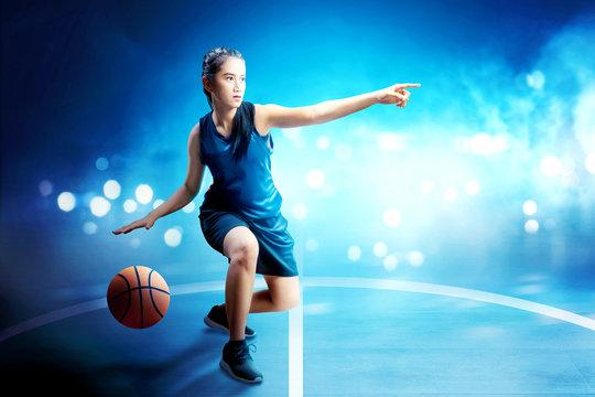 Beautiful asian woman in basketball uniform dribbling the ball