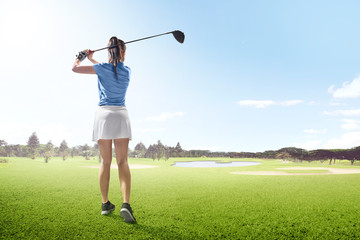 Rear view of asian woman on long drive swing with wood club in the golf course with sand bunkers, pond and trees