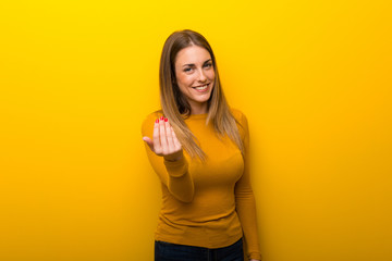 Young woman on yellow background inviting to come with hand. Happy that you came