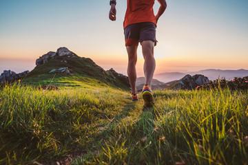 Fototapeta Man trail running on a mountain at the dask obraz