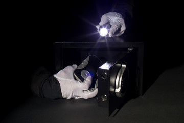 a thief stealing digital data from a safe in white gloves