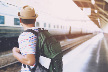 The passengers are stand waiting for the Station platform. Young man traveler with backpack looking waiting for train. the tourist travel Get ready for departure concept.