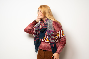 Hippie woman over white wall listening to something by putting hand on the ear