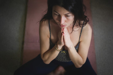 Gorgeous young Europian female on dark background, holding hands in namaste or prayer,  keeping eyes closed while practising yoga and meditating at home alone, having calm look on her face. Top view