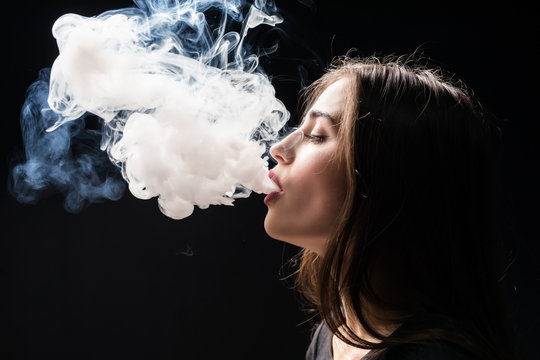 Young woman smoking electronic cigarette vaping a cloud of smoke isolated on dark background