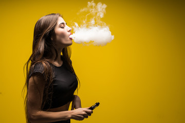 Young woman standing and vaping a cloud of smoke on yellow background.