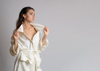 Portrait of beautiful woman in white dress or bathrobe with wet style hair on white background. Place for text. Copy space