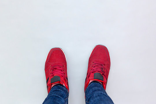 Feet in sneakers on gray background, top view. Youth Selphie Modern hipster.
