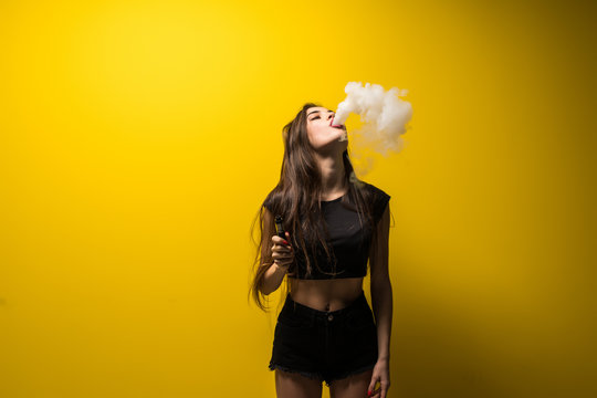 Young woman standing and vaping a smoke on yellow background.